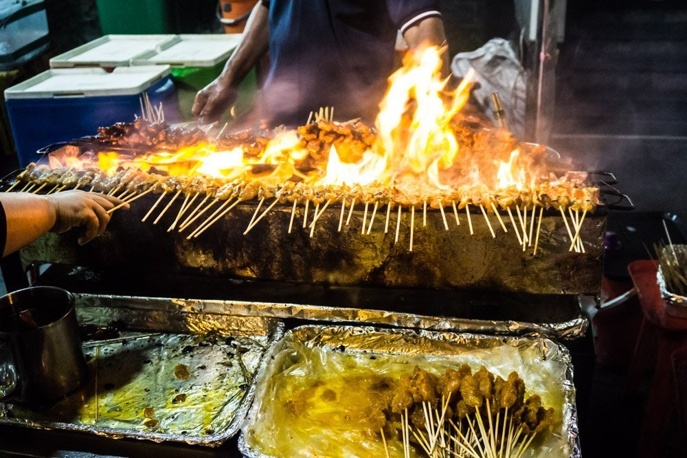Satays: Skewers of meat cooked Malay style with Tumeric over an open grill. Stalls are not restricted to any race, and can be operated by Chinese, Malay, or Indian merchants. Typical meats are chicken, beef, prawns, and lamb (pork with the Chinese operators only). Delicious and cheap.