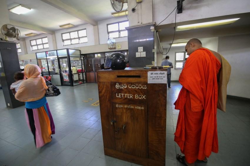 Letter box and munk in Kandy, Sri Lanka