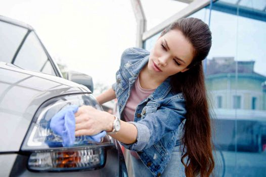 attractive woman cleaning car headlight at car wash with rag