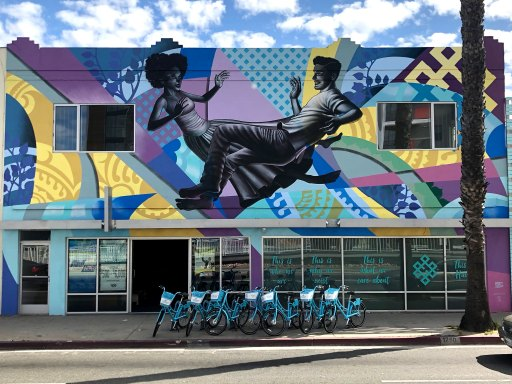 a storefront with a mural applied to its facade of a woman and man floating in space against an abstract blue, purple and yellow background