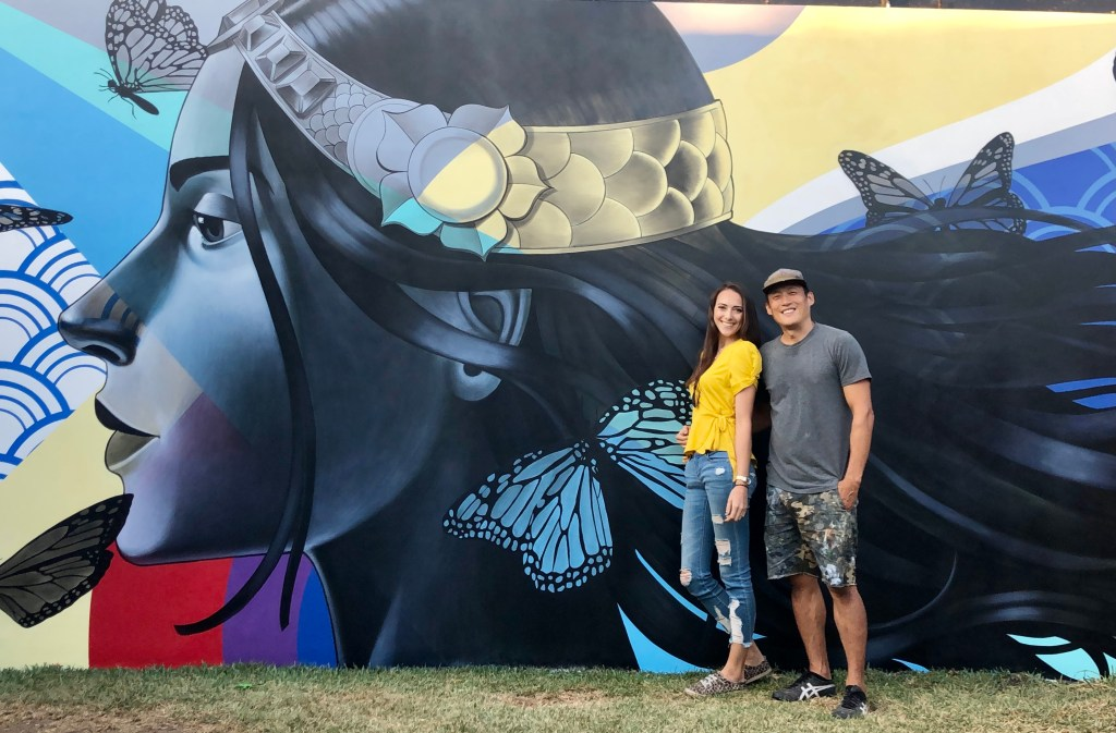 Julie Hunter and John Park stand together in front of a mural depicting a woman's profile with butterflies encircling her head