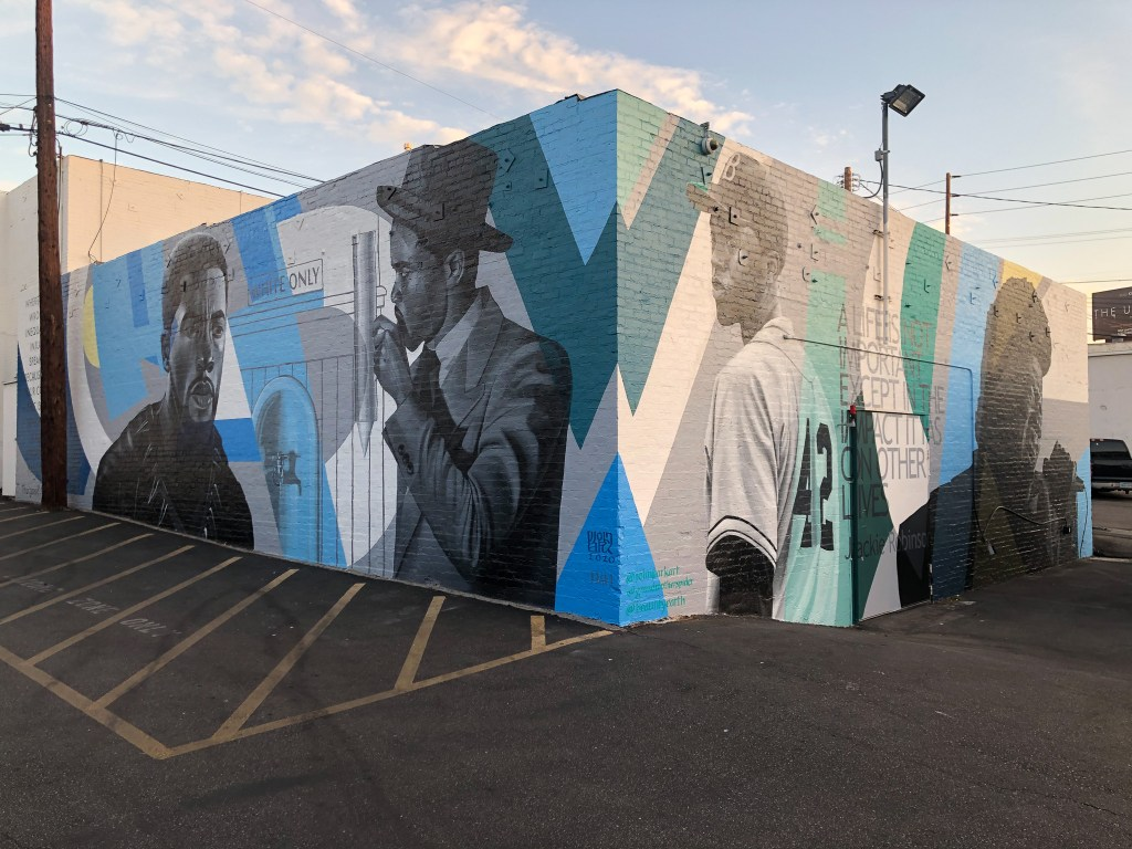 The corner of a low brick building where two facades are visible and painted with images of actor Chadwick Boseman with an abstract geometric background in shades of blue and green