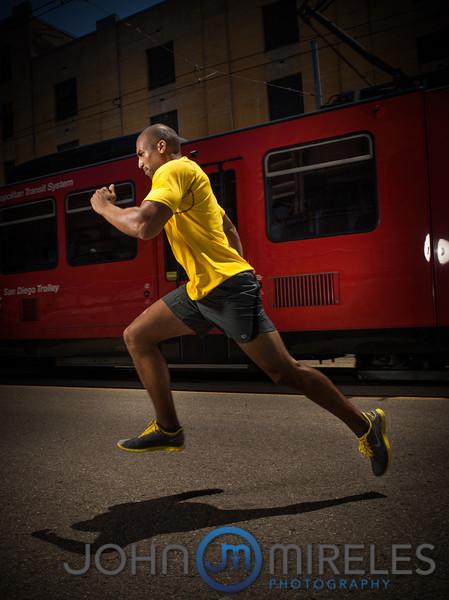 Man runs in urban setting, trolley in background