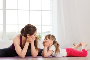 Young mother talking with daughter during yoga exercise