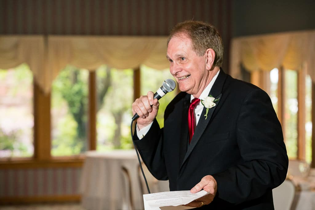 brides dad gives a speech and laughs.