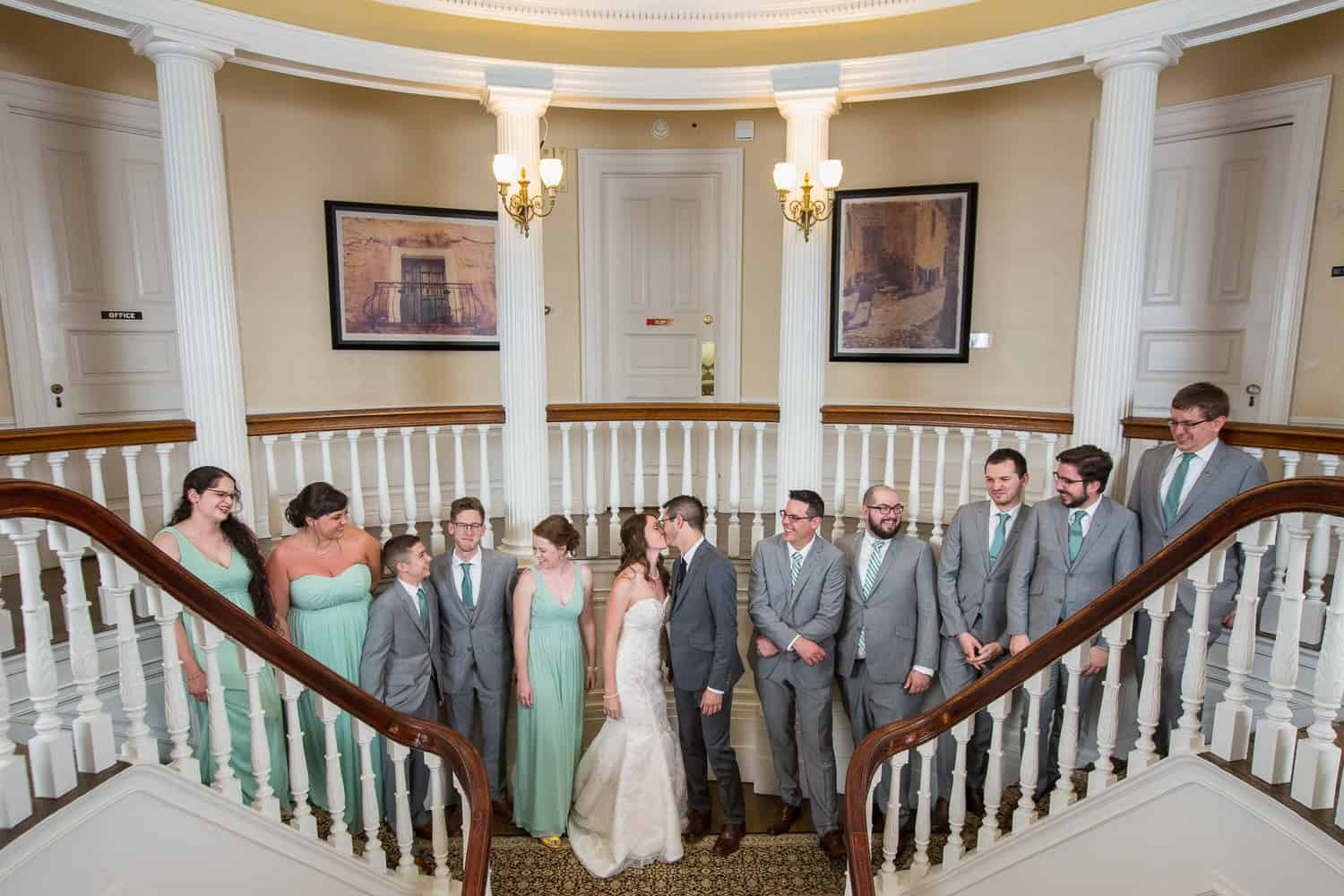 wedding party standing on a large split stairway.