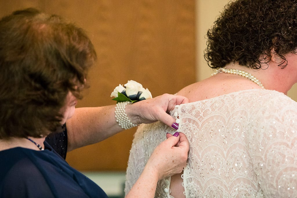 Mom buttons up bride's dress.