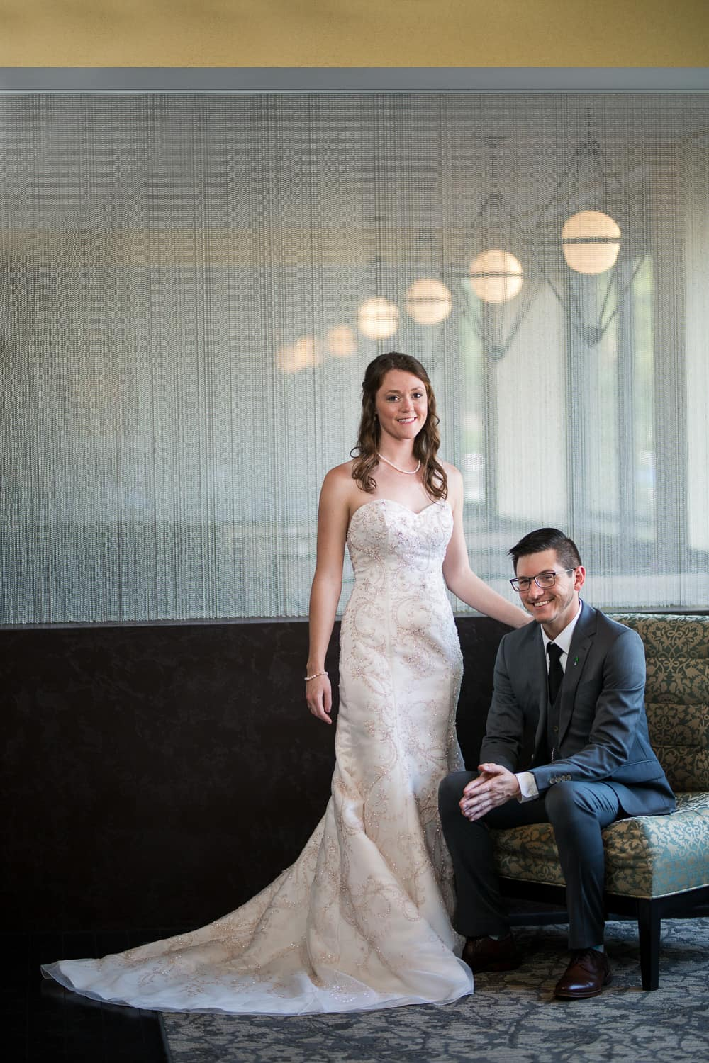 groom in grey suit is sitting while his tall bride stands next to him. a curtain of metal beads is behind them.