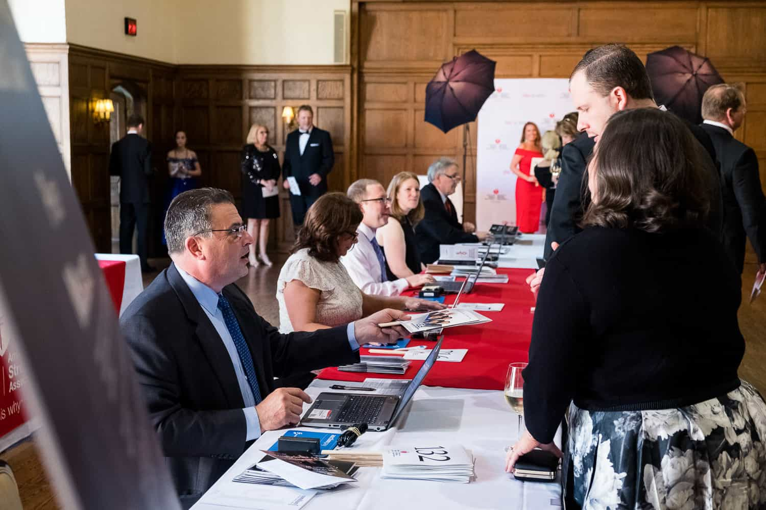 Event photography of volunteer signing in a guest at American Heart Association Heart Ball.