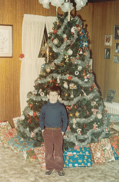 4 or 5 yr old John in a brown pants and blue turtle neck standing in front of the christmas tree.