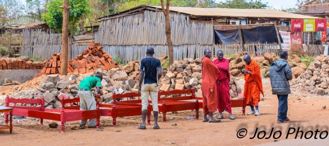 Roadside furniture store - Maasai man painting bed.