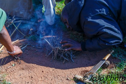 Maasai warriors use dried zebra dung, machete, and sticks for fire building.