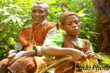 Batwa Pygmy Elder with woman weaving basket in Bwindi National Park