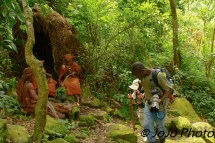 Porter helps Mary visiting Batwa Pygmy Tribe in Bwindi National Park