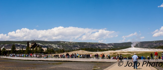 People wait for Old Faithful to erupt
