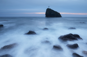 Seascape with rock with a cross. Long exposure. Rock St. phenome