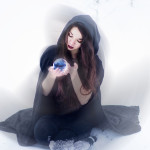 Witch or woman doing magic in black cloak with glass ball in whi