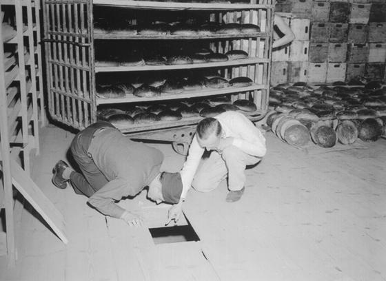 Американские лейтенанты Роберт Р., Роджерс (слева) и Эрих Пинкау из немецкой криминальной полиции осматривают пекарню и укрытие Лейпке Дистел, члена еврейской группы мести Накама