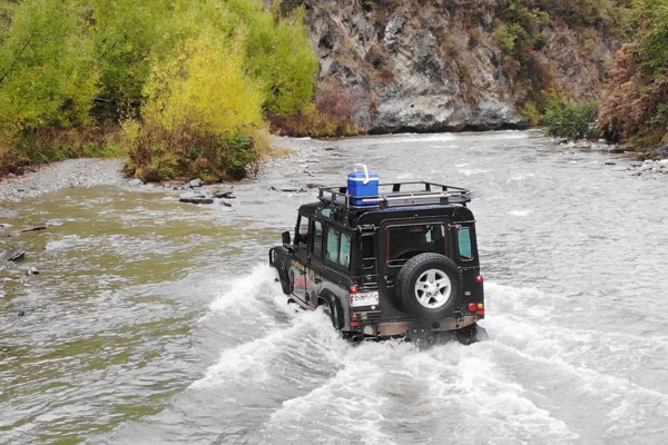 Defender driving through the water in Queenstown