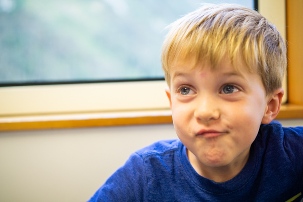 Milford Sound boy making silly face on ship