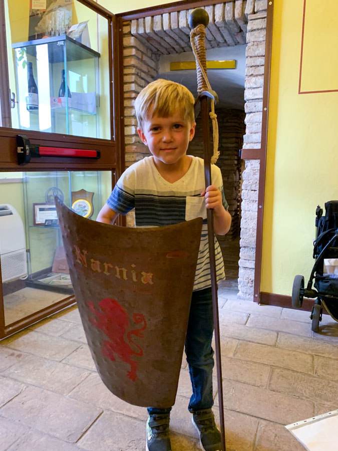 Narni sotteranea boy holding shield and sword