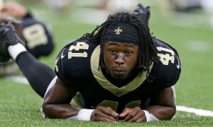 Alvin Kamara lays down in the grass