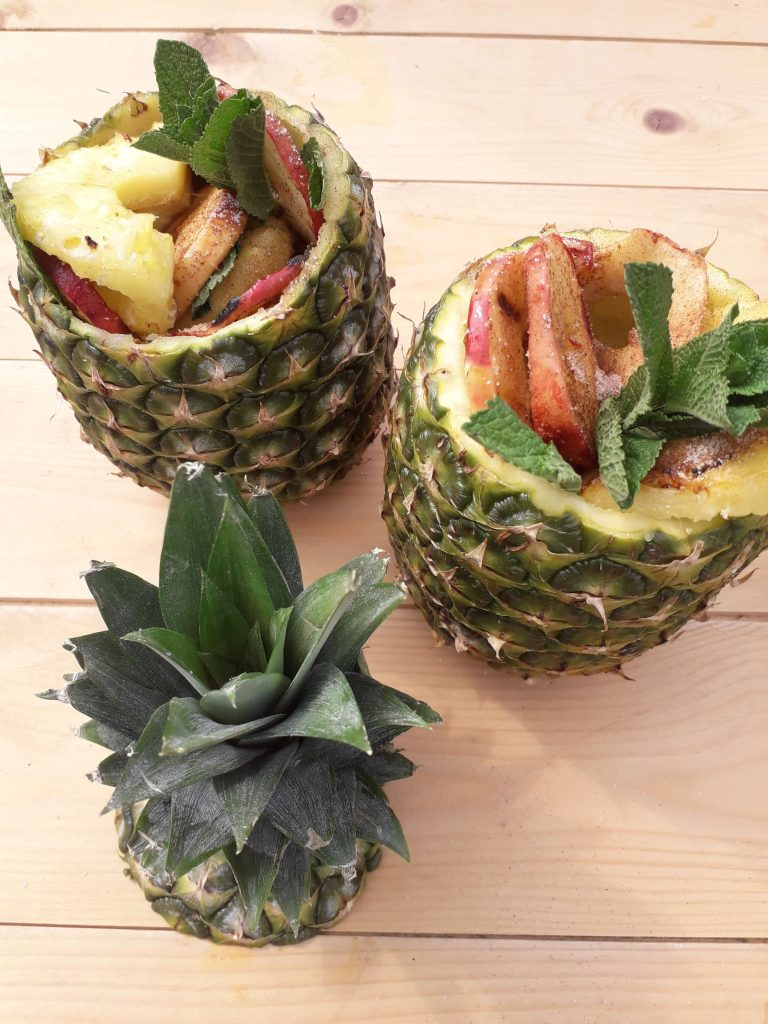 Grill slices of apples and pineapples then dust with sugar and cinnamon. Serve inside hollow pineapple