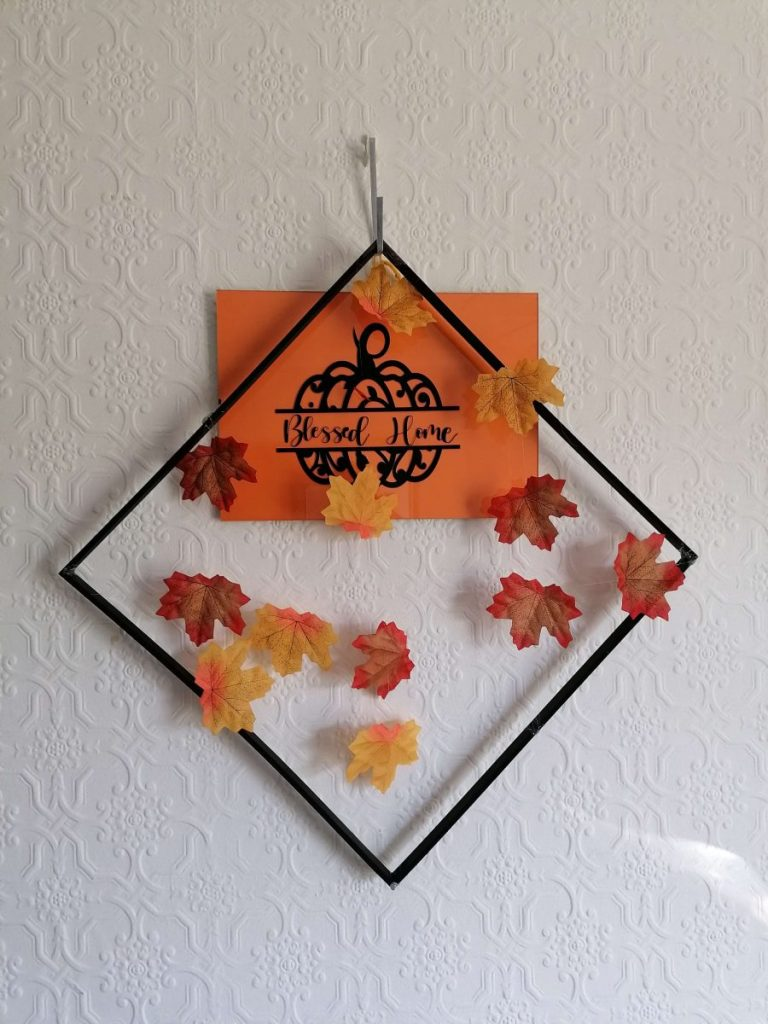 a Fall wall hanging made with faux Fall leaves ready for decorating for fall on a budget.