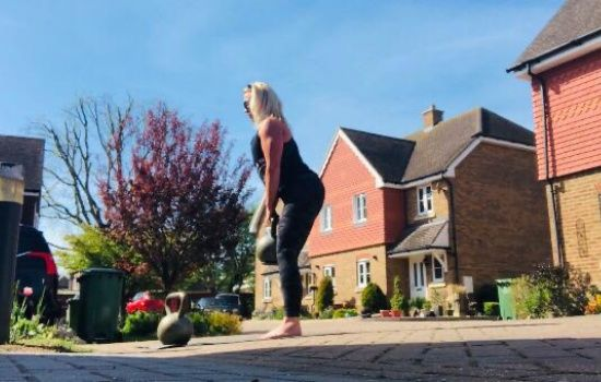 woman lifting kettle bell outside a house