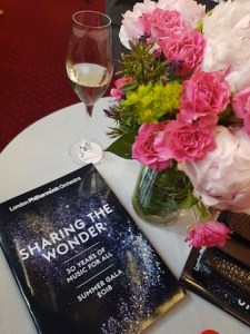 LPO Summer Gala table laid with a programme, champagne and flowers
