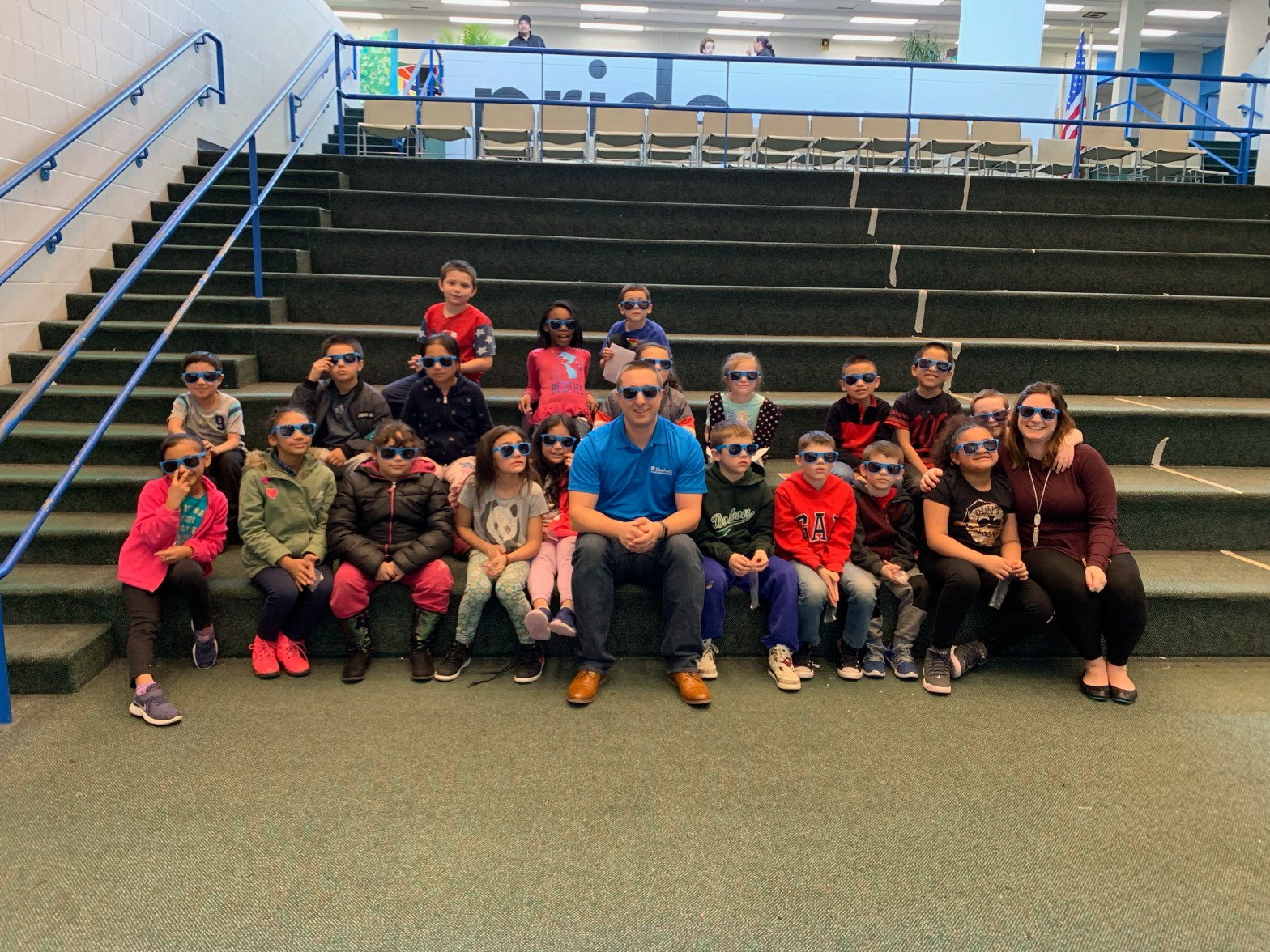 A group of kids, a teacher, and Jonathan sitting on steps all wearing Bluehost sunglasses.