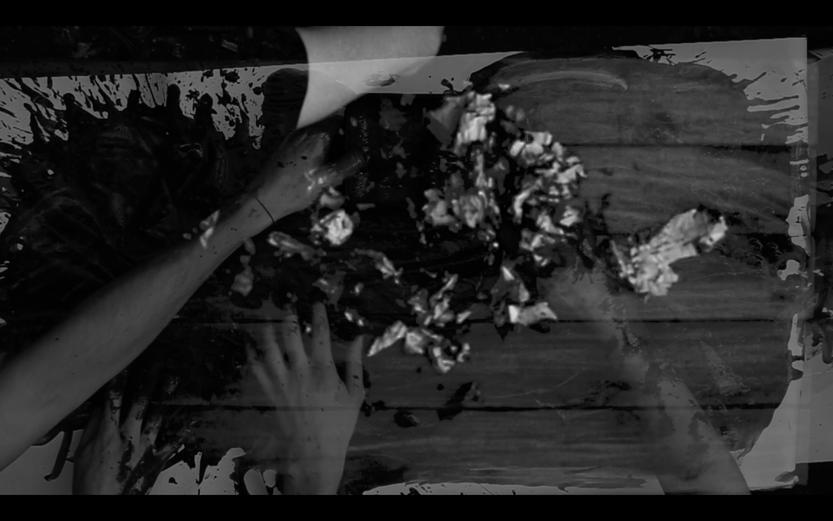 A blurred black and white video screenshot featuring hands screwing up bits of paper.