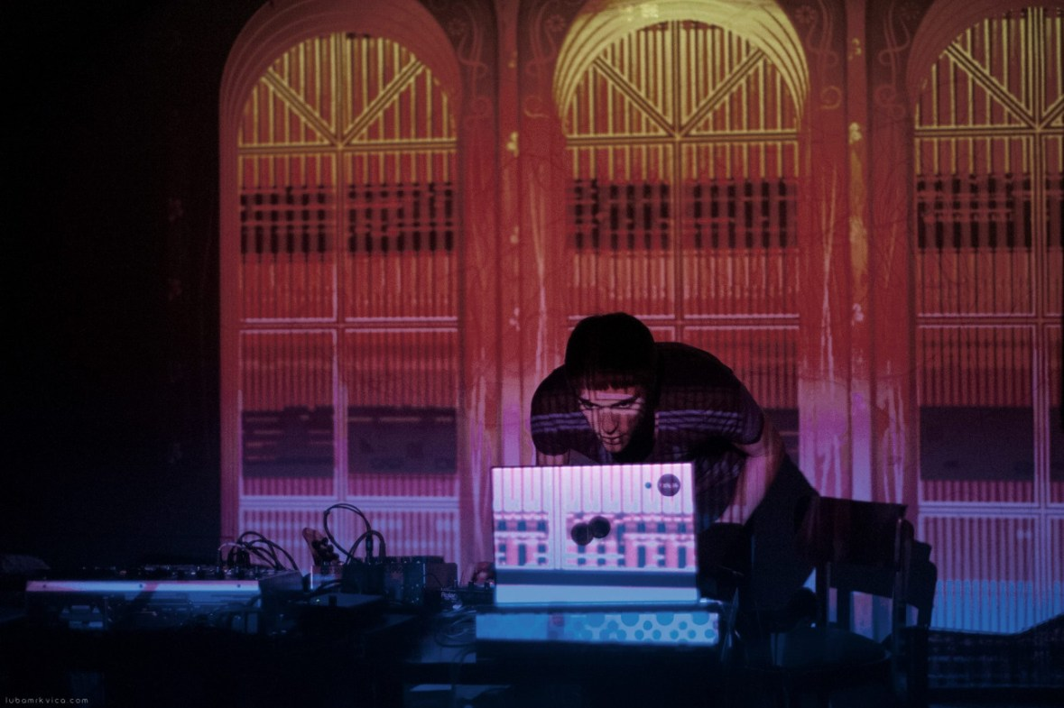 Jonathan Fox playing music in a club behind a laptop with a projection on top.