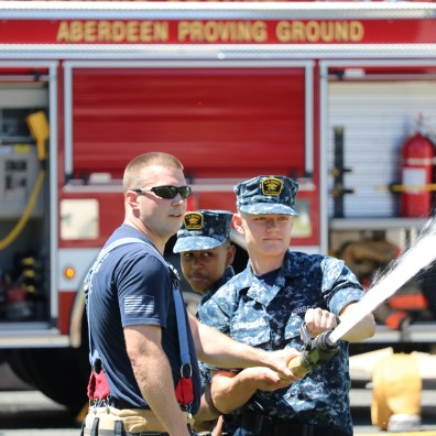 Harrison Henneberg, 16, of Clifton, Virginia (right) operates the fire hose nozzle as Joseph Telfer, 14, of Baltimore, (center) handles the hose and APG firefighter James Smith, left, supervises during an exercise at the APG South (Edgewood) fire station on Monday, July 1, 2019. Harrison and Joseph are two of more than 160 members of the U.S. Naval Sea Cadets Corps, who are taking part in a 9-day camp at APG. In addition to firefighting and emergency management skills, the cadets — ages 13-17 — will spend their time at the installation learning military customs, Naval history and leadership lessons.