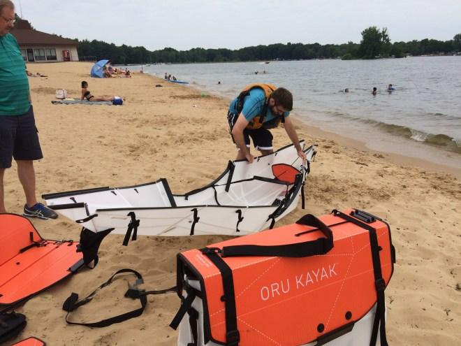 Photo of Oru Kayaks being folded on the beach.