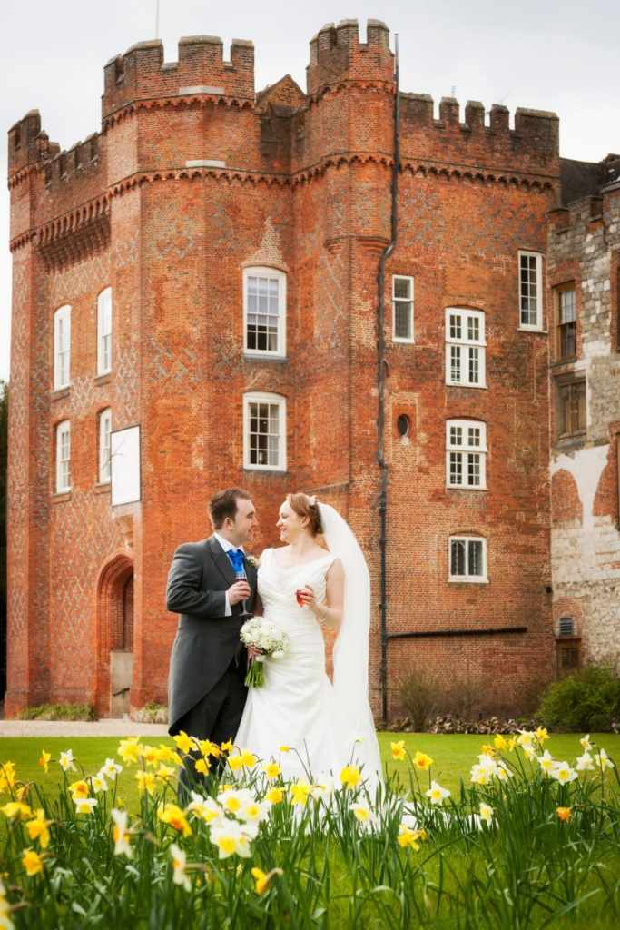 Bride and groom and daffodils at Farnham Castle