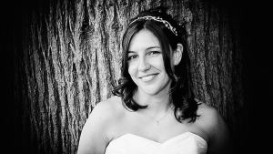 Bride leaning on a tree