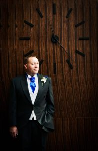 Groom by big clock at Harbour Hotel, Guildford