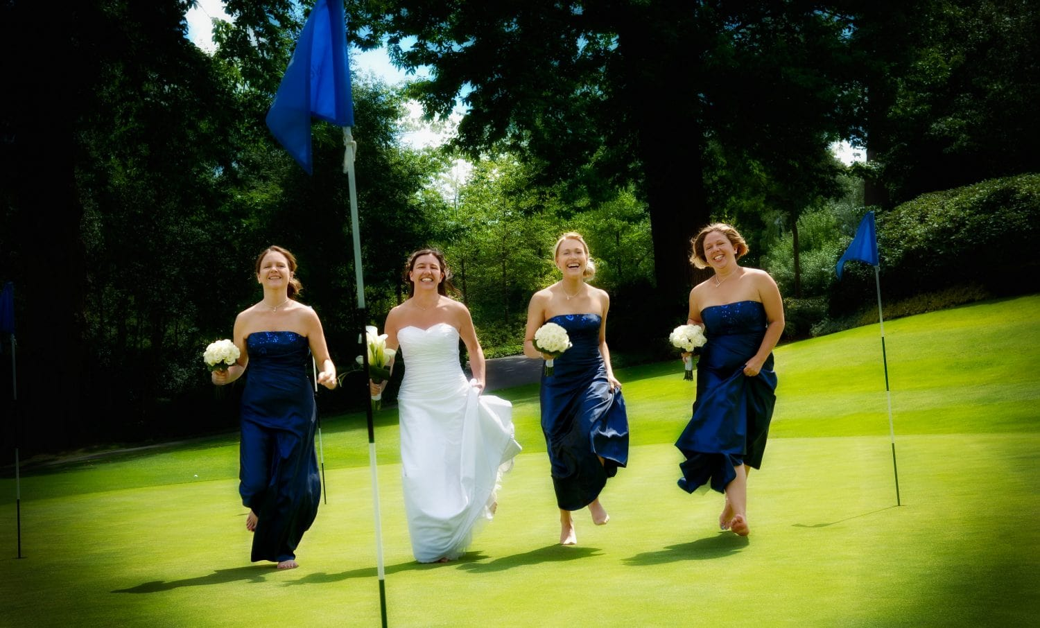 Bride and bridesmaids running across the green at Wentworth Club