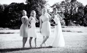 Bide and bridesmaids striking a pose at Mellow Farm Barn, Dockenfield