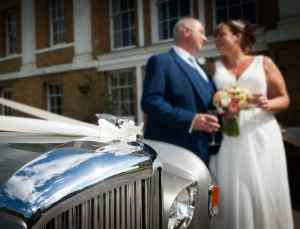 Newly weds by the Bentley wedding car