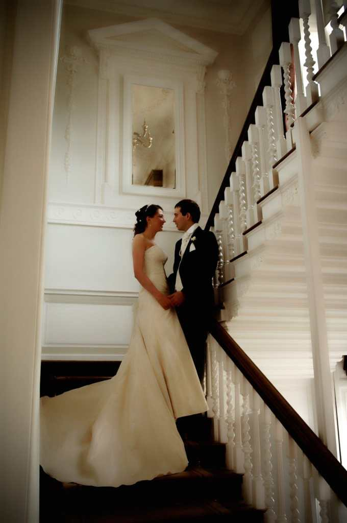 Bride and Groom have a romantic encounter on a grand stair case at warbrook Park