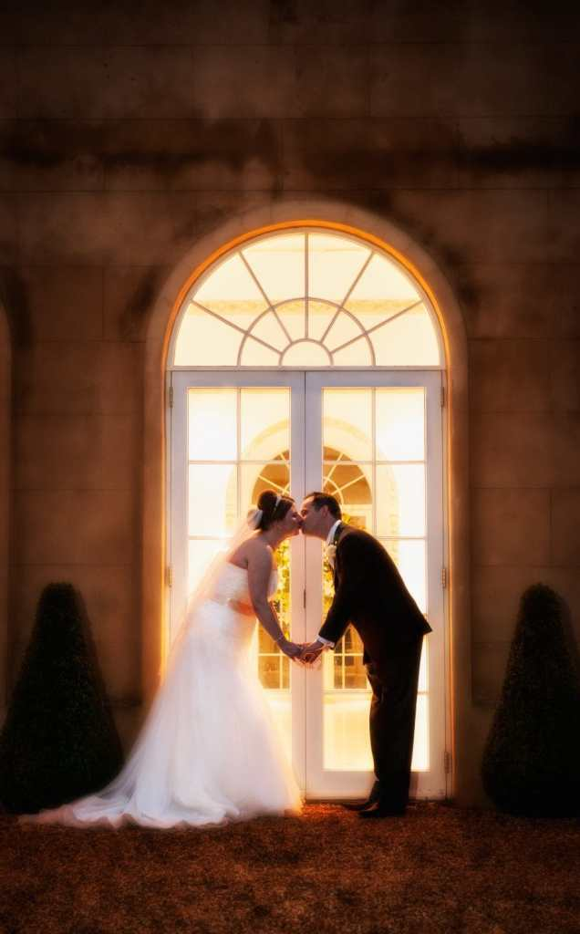 A goodnight wedding kiss outside the vine room at Northbrook Park, Farnham