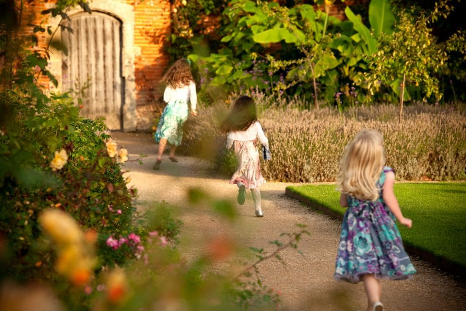 Girls running through The Walled Garden at Cowdray, wedding