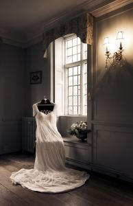 Vintage wedding dress on a chair by the window