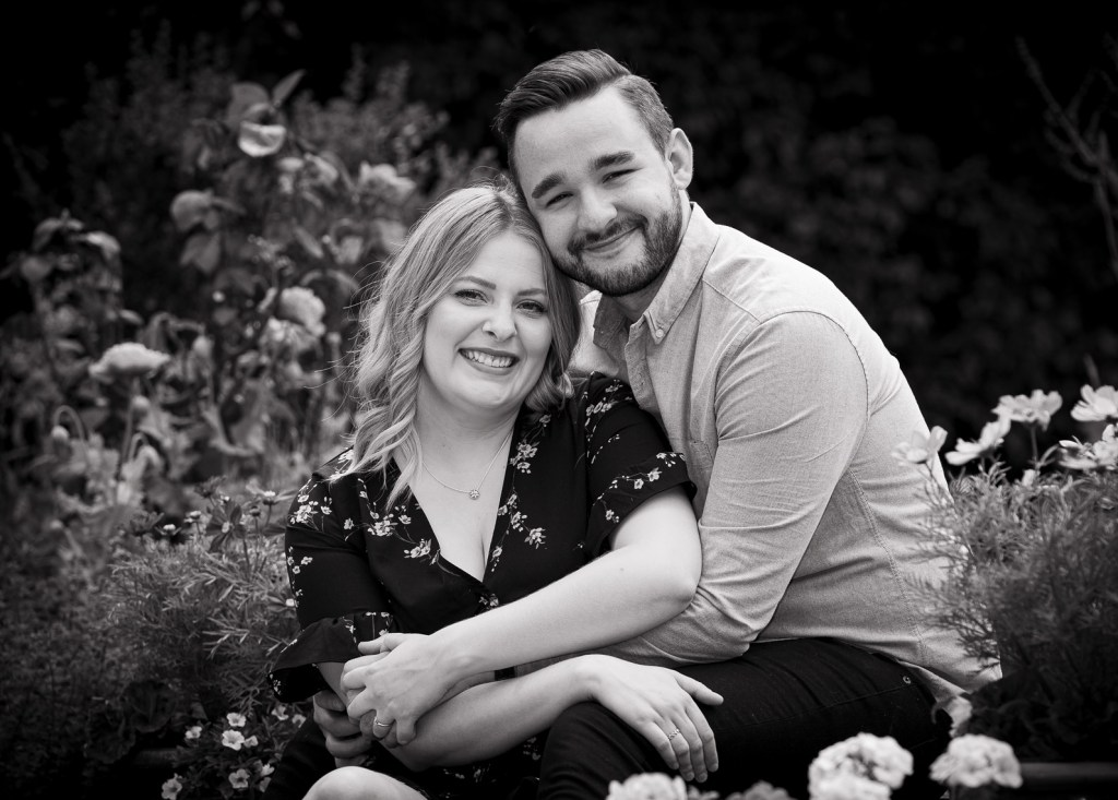Black and white engagement of a couple sitting on the steps in a garden