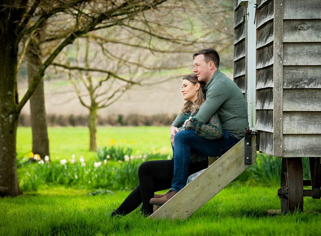 Couple sitting on the steps of a shpherds hut