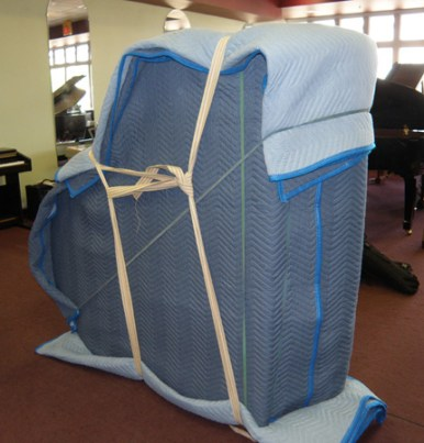 After being wrapped in the pads, the piano is strapped to keep everything in place.
