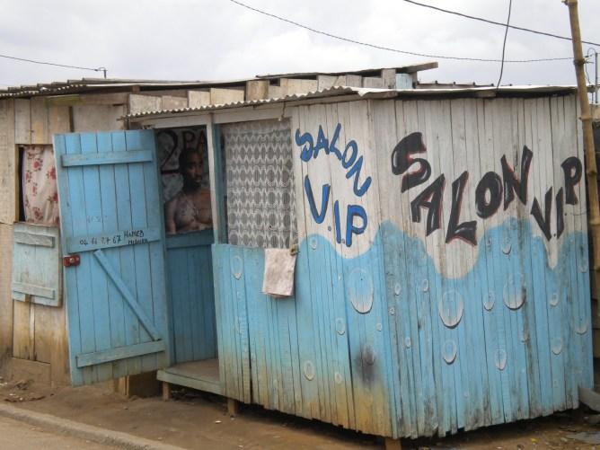 Signs in Abidjan play on themes of work, consumption, and Abidjan's cosmopolitan self-image.