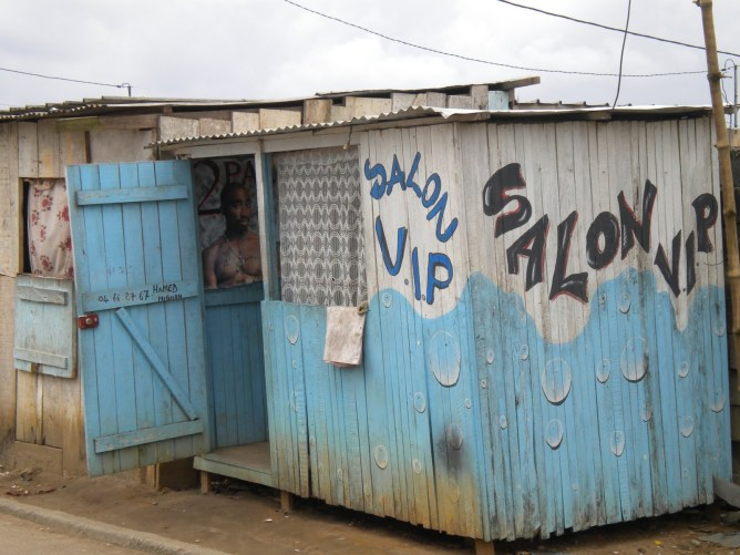 Signs in Abidjan play on themes of work, consumption, and Abidjan's cosmopolitan self-image.